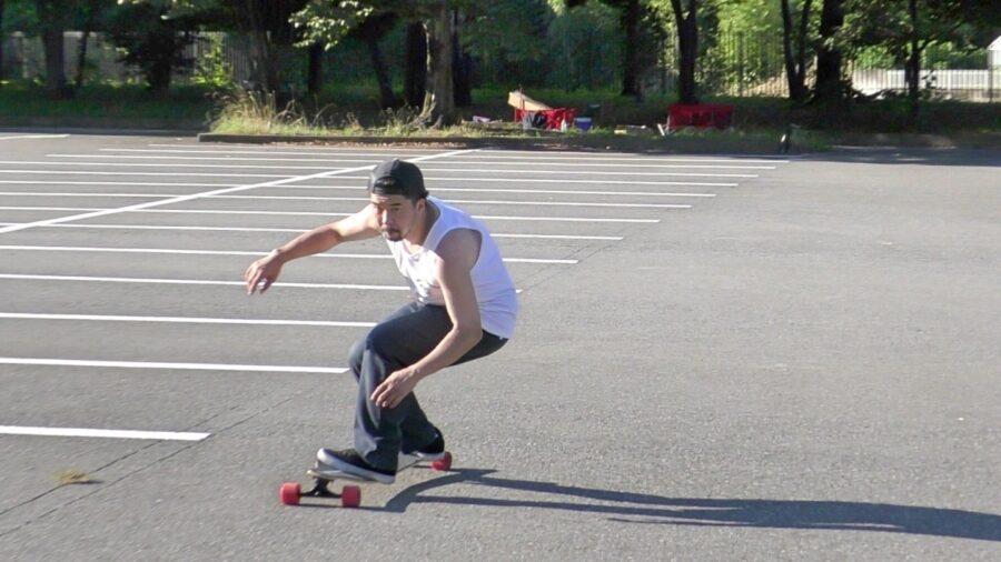 ロングスケートボードでスノーボードのオフトレをするプロスノーボーダー藤沼到